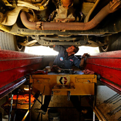 DENVER, CO - NOVEMBER 11: Julio Vergara works on doing and oil change, at a Grease Monkey in east Denver, on a truck owned by active army soldier Luke Goeckner, November 11, 2013. Veterans got a free oil change at many Grease Monkey locations for Veterans Day. (Photo By RJ Sangosti/The Denver Post)